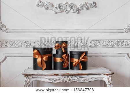 Wrapped gift black boxes with ribbons as Christmas presents on a table on luxury white wall design bas-relief stucco mouldings roccoco elements.