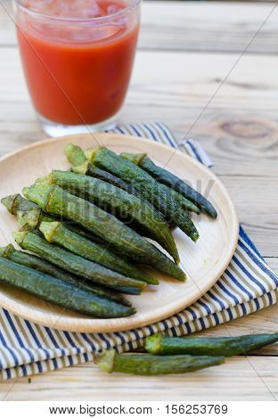 Okra chips on wooden plate and tomato juice
