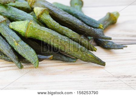 Okra chips on wooden table, healthy eating
