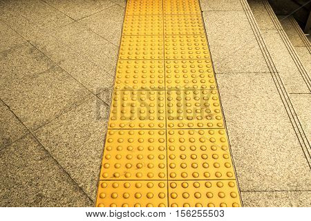 Sidewalk guides for blind. Yellow concrete cobblestones on walkway for blindness people.