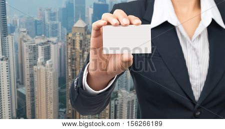 Businessman's hand holding blank cardboard in front with blur building background.