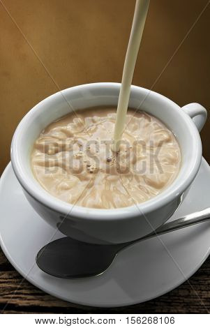 milk poured in a coffe cup abstract background.