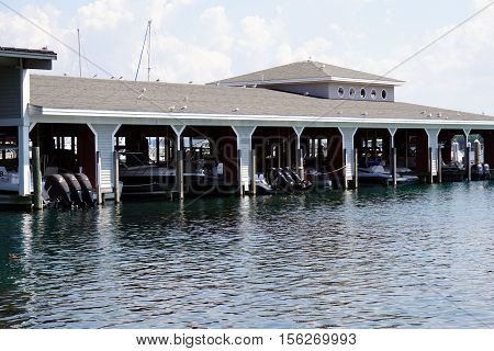 HARBOR SPRINGS, MICHIGAN / UNITED STATES - AUGUST 3, 2016: Boats are docked in slips in the Walstrom Marine boathouse in Harbor Springs.
