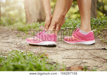Woman Runner Holding Her Twisted Ankle After Running Exercise Outdoors. Female Jogger In Pink Sneake