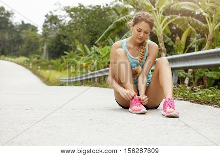 Young Beautiful Blonde Girl Athlete In Sportswear And Pink Sneakers Tying Laces While Having Break D