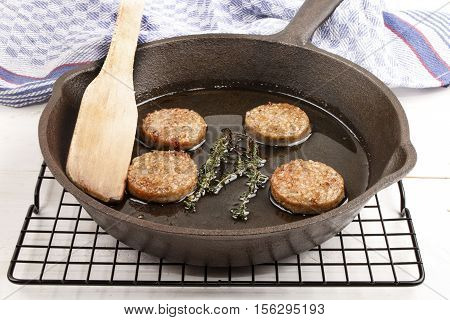 fried irish home made white pudding with oil in a cast iron pan