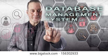 Happy smiling but uncompromising male database expert is touching DATABASE MANAGEMENT SYSTEM on an interactive control screen. Information technology concept and data management metaphor.