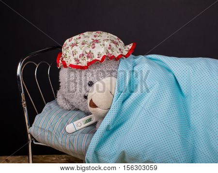 Sick lonely teddy bear lying with thermometer in bed in a room with a black background