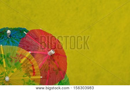 Open cocktail umbrellas displayed on a yellow background