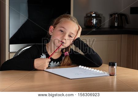 Young girl daydreaming and holding her pencil against her mouth while doing her homework.