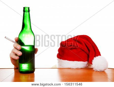 Person in Santa's Hat with the Beer and Cigarette at the Table on the White Background