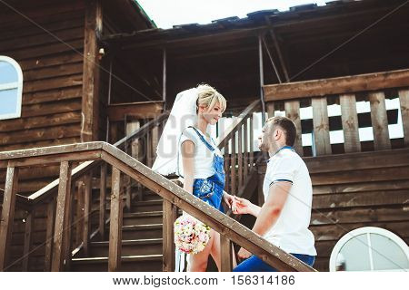 Happy young bride and groom. Wedding in rustic style. They embrace near the wooden porch.