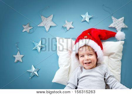 Sleepy child on blue blanket in red hat. Cute baby sleeping in christmas cap
