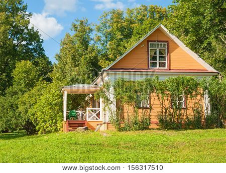 Small wooden house with a porch on the lawn in the forest