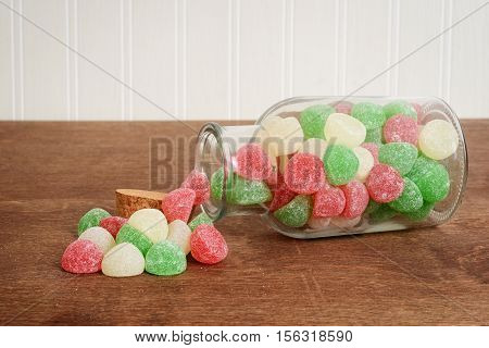 spilled jar of christmas gum drops candy on wood table
