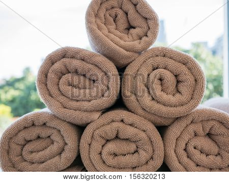 Pile of rolled up spa brown towel