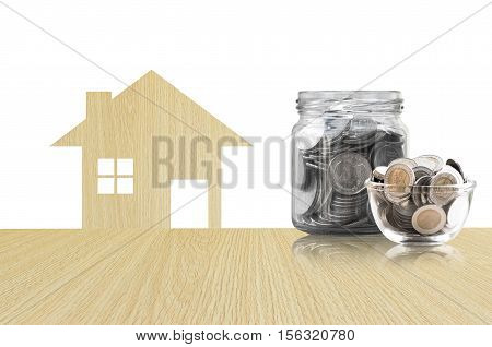 coins in a glass jar of buying a new house - saving money for future concepthouse savings coins. isolated on white background