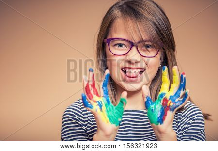 Portrait of a little pre-teen student girl showing painted hands. Toned Photo.
