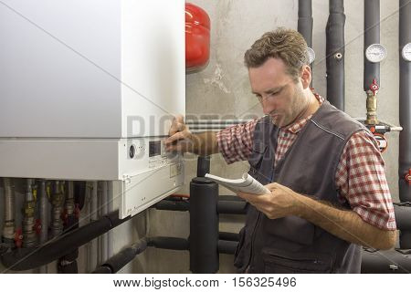 Plumber Who Carries Out The Maintenance Of A Condensing Boiler
