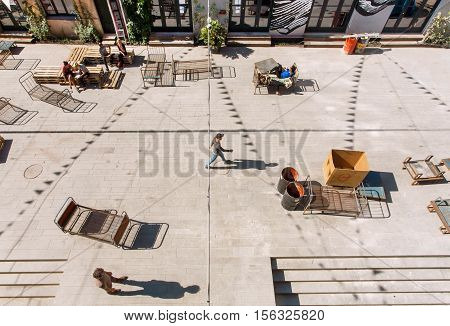 TBILISI, GEORGIA - OCT 9, 2016: Man walking in urban part of city with artistic galleries and weird benches around on October 9, 2016. Tbilisi has a population of 1.5 million people