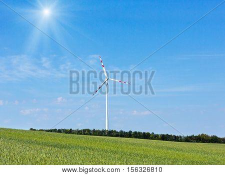 Wind turbine on blue sunshiny sky background