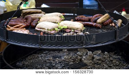Street food barbecue meat sausages and sandwiches cooked on the grill.