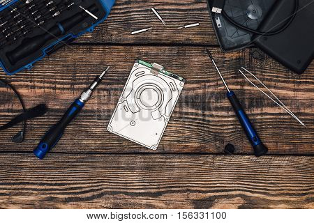 HDD with Professional Precision Screwdriver and Some Tools on Wooden Table
