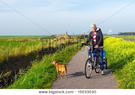 Man with his dog at the bike in Dutch landscape