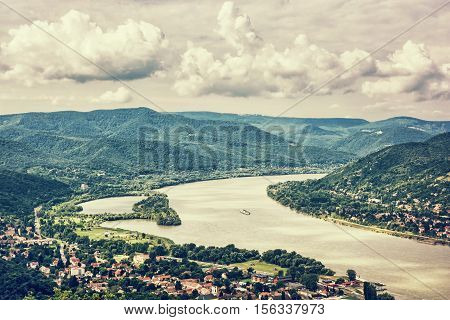 View from Ruin castle of Visegrad Hungary. Danube river. Travel destination. Retro photo filter. Sightseeing cruises. Forests clouds and flowing water.