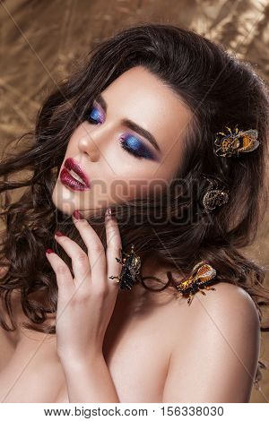 Beauty woman face with beautiful make-up colors. Dark hair wavy hair ornaments in the form of wove clear skin beautiful face. Portrait shot in studio on a gold background.