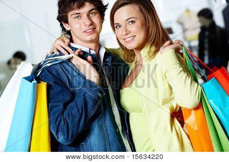 Retrato de casal de amar depois de comprar presentes, olhando para a câmera com sorrisos