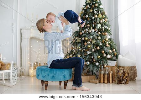 Slim young mother,a woman with blond hair gathered at the nape,spends time with young son near Christmas festive Christmas tree in the room with the white floor,both dressed in blue shirts and dark blue jeans,a Christmas portrait