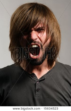 Screaming young man with a beard and long hair