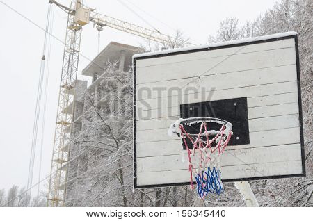 Snow-covered basketball hoop with industrial background. torn mesh basketball hoop