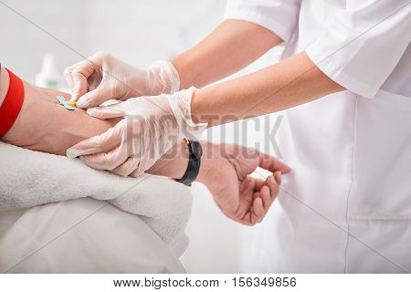 Close up of doctor arms sticking needle into male arm for blood sampling