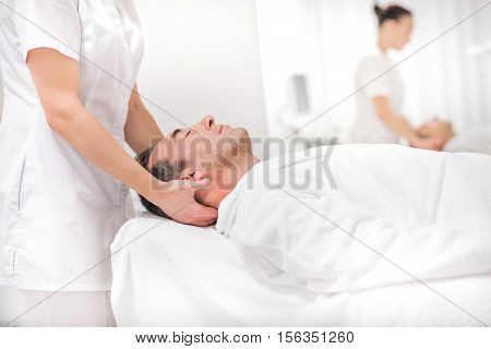Middle-aged man is lying on massage table at beauty salon. Masseuse is standing and pampering his head. His eyes are closed with satisfaction