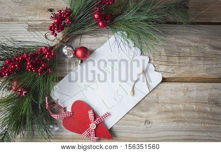 horizontal image of a child's wish list with a broken wish bone lying on the paper with a little wood heart and green fern and cranberry lying above the note on rustic wood background.
