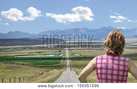 horizontal close up image of caucasian woman with back facing the camera standing at the end of a long straight dirt road her gaze on the mountains in the distance on a beautiful summer day.