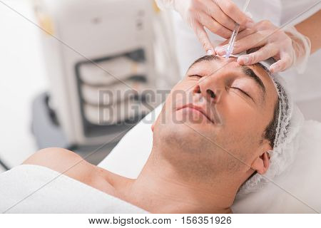 Close up of doctor hands injecting botox into male forehead. Man is lying with closed eyes