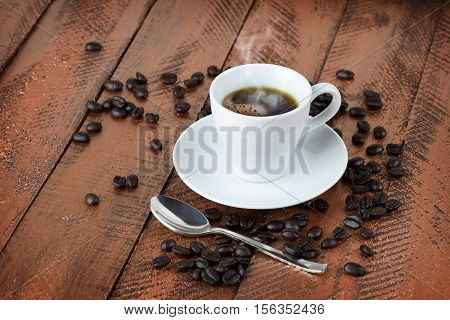 Cup of coffee and coffee beans on the wooden background. Close-up. Habits. Traditions.