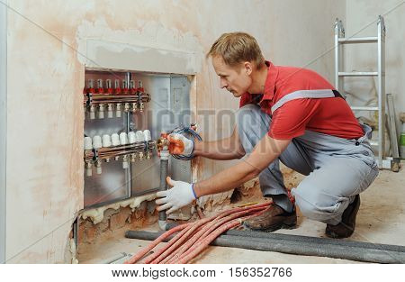 Installation of home heating. A worker attaches the tube to the collector heating.