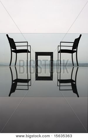 two chairs and table on landscape with hills and city