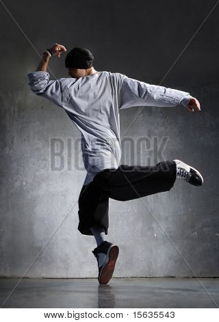 cool looking hip-hop dancer posing on old wall