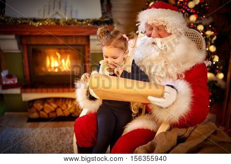 Sweet little girl in Santa Claus lap undecided choosing her present from list, childhood in Christmas