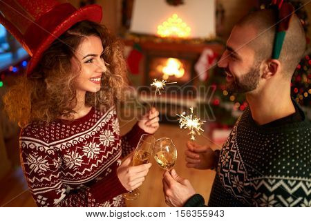 Young couple celebrate New Year's eve with sparkles and sparkling wine