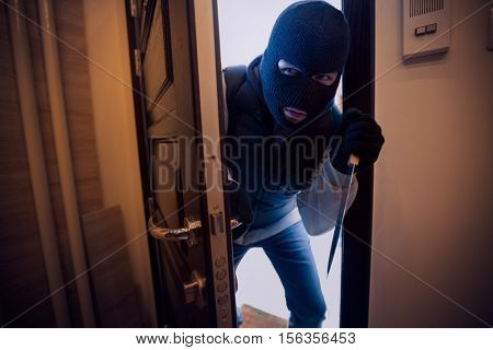 dangerous burglar sneaking into the house with a knife in his hand