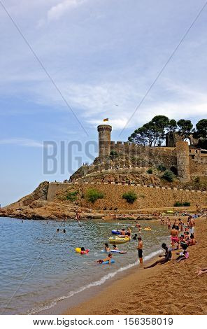 Tossa De Mar, Spain - August 1, 2014: View of the medieval walled town Vila Vella and town beach in Tossa de Mar.