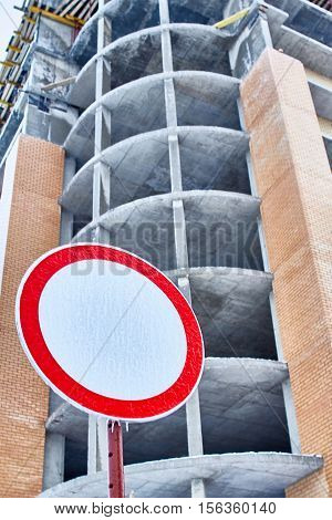 Red circular prohibiting road sign. Unfinished building in background.