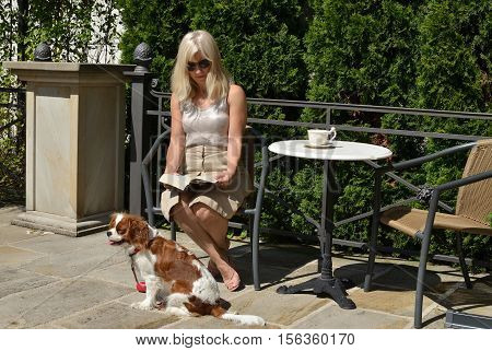 Blonde woman sitting in elegant garden with her pet - Cavalier King Charles Spaniel - reading a book and drinking coffee