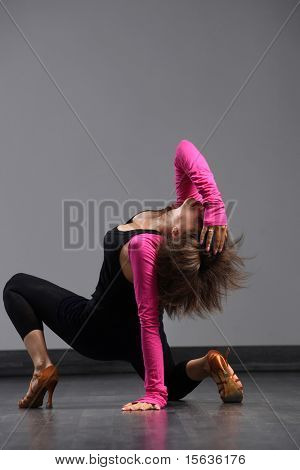 young and stylish dancer posing on grey